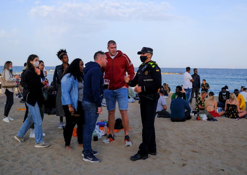 A police office speaks with tourists after vacating a party at Barceloneta beach, in Barcelona