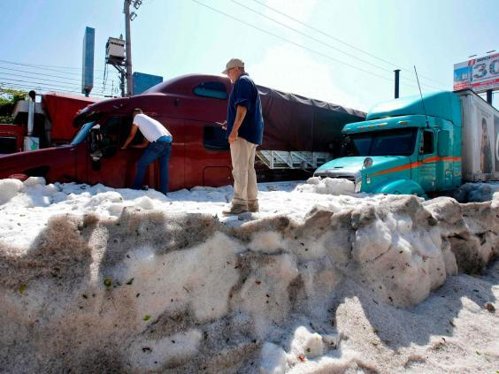 Men remain next to trucks buried in hail in the eastern area of Guadalajara, Jalisco state, Mexico (AFP/Getty Images)