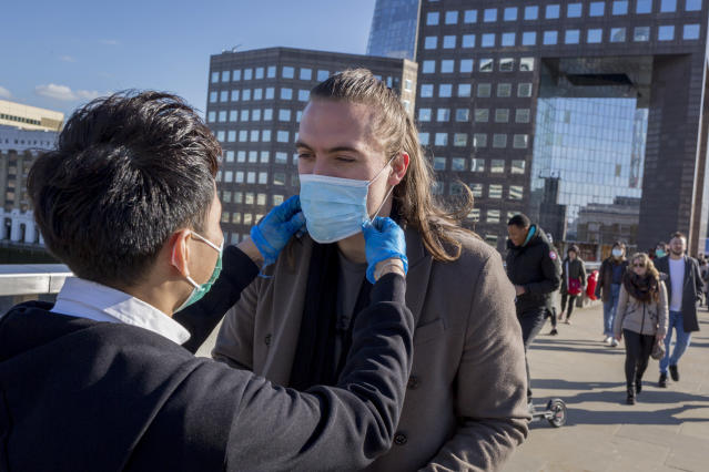 People are pictured handing out free masks to commuters on London Bridge on 16 March. The UK has had 1,551 confirmed cases. (Getty Images)