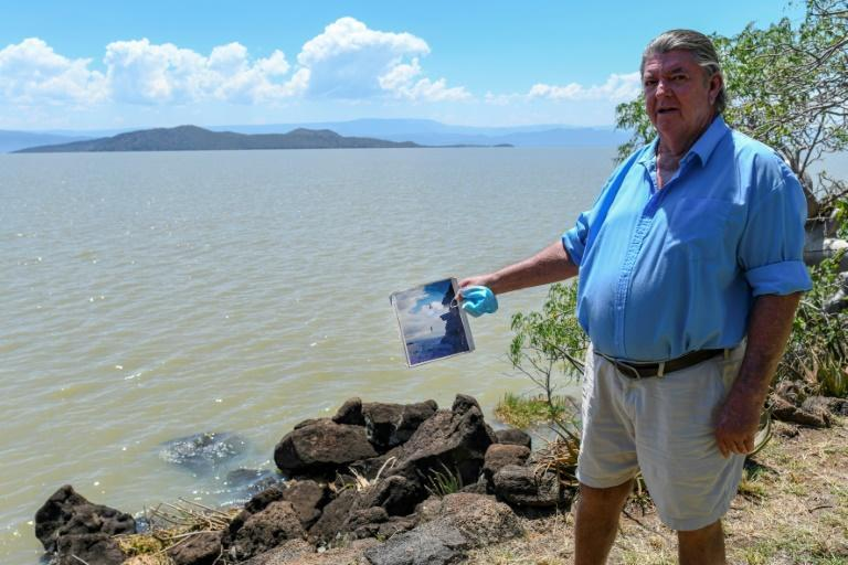 Murray Roberts, 69, holds an old photo of his sons jumping off a cliff face into the lake from the edge where he is standing that is now submerged