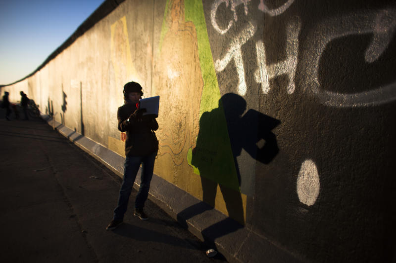 In early morning light, a radio broadcast journalist casts her shadow on the East Side Gallery named part of the former Berlin Wall as she reports about protests in Berlin, Monday, March 4, 2013. After massive protest over the last days an investor suspended the removal of a section of the historic stretch of the Berlin Wall known as the East Side Gallery to provide access to a riverside plot where luxury condominiums are being built. (AP Photo/Markus Schreiber)