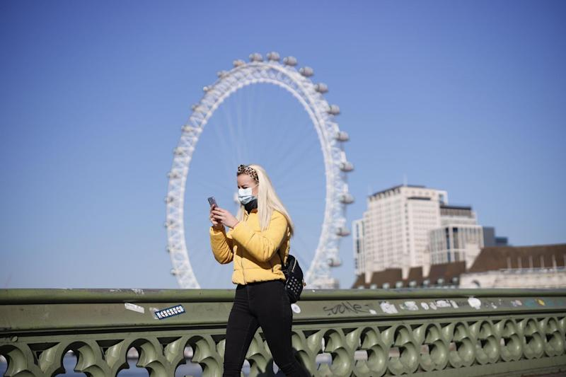 A pedestrian wearing a protective face mask walks across Westminster Bridge on Wednesday (AFP via Getty Images)