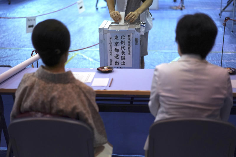A voter casts a ballot in the upper house elections as representatives of a local election administration commission observe at a polling station in Tokyo Sunday, July 21, 2019. Voting started Sunday morning for the upper house elections where Japanese Prime Minister Shinzo Abe's ruling coalition is seen to retain majority, according to local media report. (AP Photo/Eugene Hoshiko)