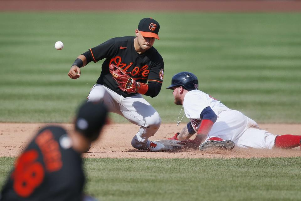 Boston Red Sox's Alex Verdugo, right, advances to second base as Baltimore Orioles' Jose Iglesias cannot handle the throw after a wild pitch by Orioles' Richard Bleier during the eighth inning of a baseball game Saturday, July 25, 2020, in Boston. (AP Photo/Michael Dwyer)