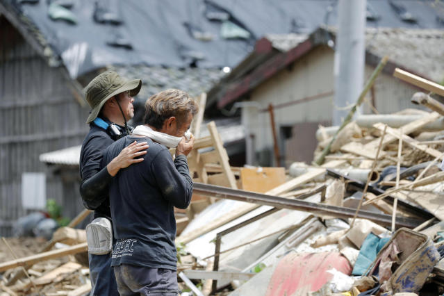 <p>Relatives react to a landslide site where three people were killed, after heavy rain hit southwestern Japan, in Uwajima, Ehime prefecture, Monday, July 9, 2018. Rescuers in southwestern Japan dug up more bodies Monday as they searched for dozens still missing after heavy rains caused severe flooding and left residents to return to their homes unsure where to start the cleanup. (Photo: Takuto Kaneko/Kyodo News via AP) </p>