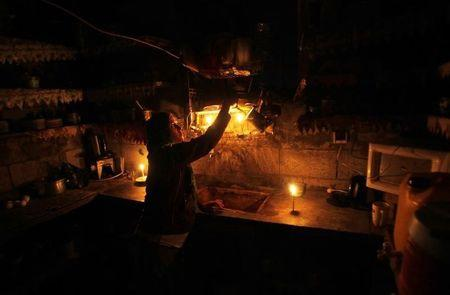A Palestinian woman works inside the kitchen of her house during power cuts in Khan Younis in the southern of Gaza Strip
