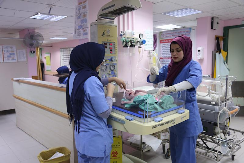 "Palestinian midwife Sara Abu Taqea (R), 23, who works in the maternity ward at Gaza's Al-Ahli hospital, weighs a newborn at the hospital in Gaza City, Feb. 10, 2019. Abu Taqea said she found temporary work in a Gaza hospital after finishing a bachelor's degree in midwifery, but that many of her colleagues were not so lucky. ""It is a six-month contract, with no guarantee of further employment,"" she said. (Photo: Samar Abo Elouf/Reuters)"
