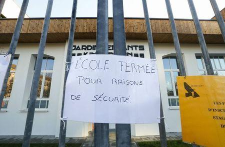 "A sign that reads ""school closed for security reason"" is pictured at the entrance of a nursery school in Brussels, November 23, 2015, after security was tightened in Belgium following the fatal attacks in Paris. REUTERS/Yves Herman"