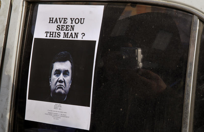 A man takes photos of a wanted notice of fugitive Ukrainian President Victor Yanukovich. (Yannis Behrakis / Reuters)