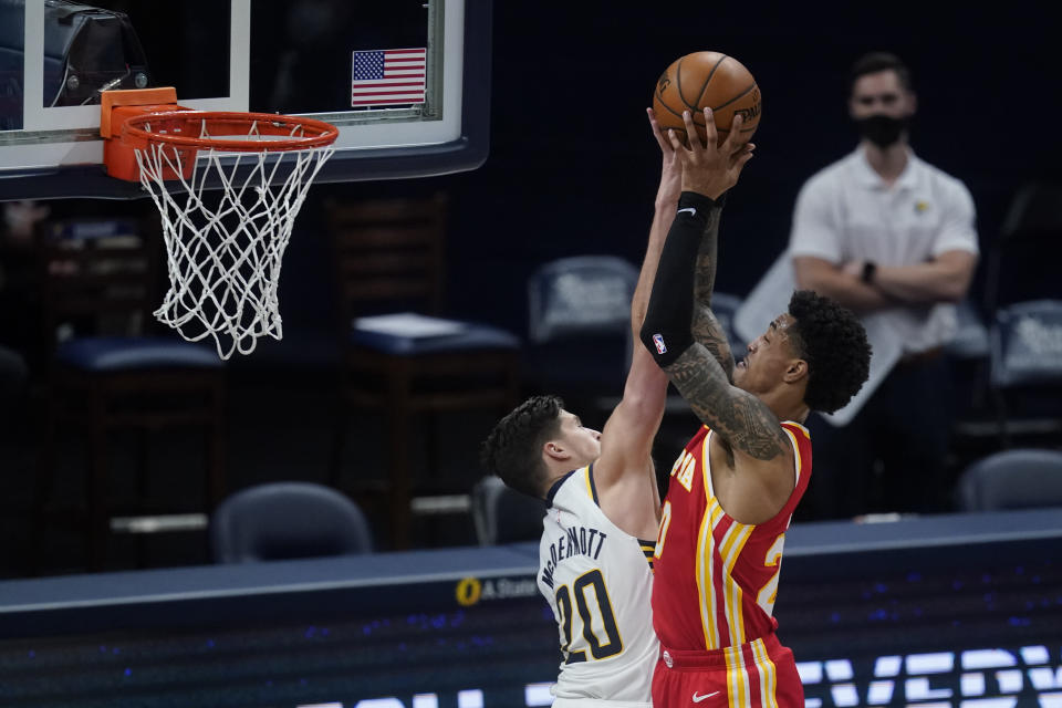Atlanta Hawks' John Collins, right, is fouled by Indiana Pacers' Doug McDermott during the second half of an NBA basketball game Thursday, May 6, 2021, in Indianapolis. (AP Photo/Darron Cummings)