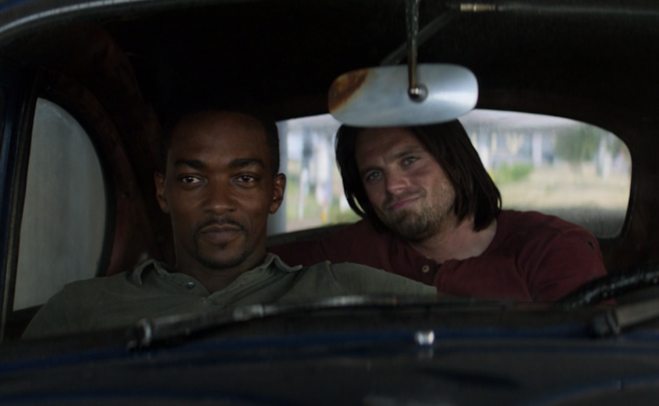 Sam Wilson smiles as he sits in the driver's seat of a car while Bucky Barnes sits behind him, smirking.