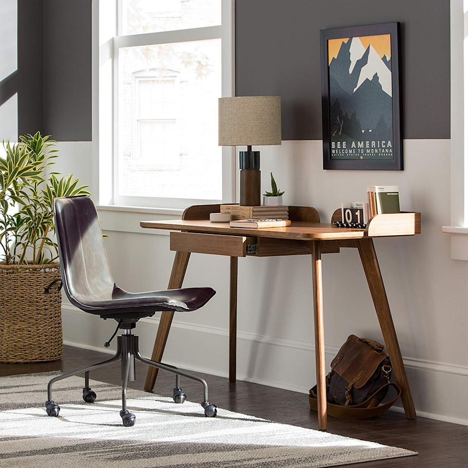 """<p>Upgrade that clunky old desk with this sleek <a href=""""https://www.popsugar.com/buy/Rivet-Mid-Century-Curved-Wood-Home-Office-Computer-Desk-403043?p_name=Rivet%20Mid-Century%20Curved%20Wood%20Home%20Office%20Computer%20Desk&retailer=amazon.com&pid=403043&price=266&evar1=casa%3Aus&evar9=45640072&evar98=https%3A%2F%2Fwww.popsugar.com%2Fhome%2Fphoto-gallery%2F45640072%2Fimage%2F45640158%2FRivet-Mid-Century-Curved-Wood-Home-Office-Computer-Desk&list1=home%20decor%2Cfurniture%2Chome%20shopping%2Cbest%20of%202019&prop13=mobile&pdata=1"""" rel=""""nofollow"""" data-shoppable-link=""""1"""" target=""""_blank"""" class=""""ga-track"""" data-ga-category=""""Related"""" data-ga-label=""""https://www.amazon.com/Rivet-Mid-Century-Curved-Office-Computer/dp/B075ZBVZST/ref=sr_1_12?s=furniture&amp;ie=UTF8&amp;qid=1546548431&amp;sr=1-12&amp;keywords=rivet+furniture"""" data-ga-action=""""In-Line Links"""">Rivet Mid-Century Curved Wood Home Office Computer Desk</a> ($266).</p>"""