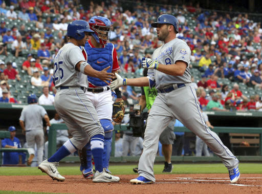 Kansas City Royals Jon Jay (25) greets Mike Moustakas (8) at the plate after a home run by Moustakas against the Texas Rangers during the first inning of a baseball game Friday, May 25, 2018, in Arlington, Texas. (AP Photo/Richard W. Rodriguez)