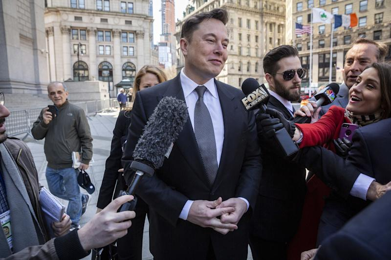 Elon Musk, chief executive officer of Tesla Inc., center, speaks to members of the media while arriving at federal court in New York, U.S., on Thursday, April 4, 2019. The SEC says Musk violated his agreement with the agency when he tweeted on February 19 that Tesla would make about half a million cars in 2019, before tweeting a few hours later that deliveries would only reach about 400,000. Photographer: Natan Dvir/Bloomberg via Getty Images