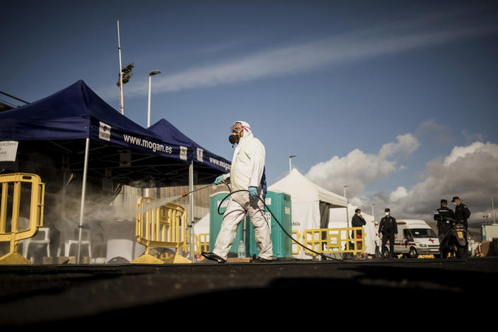 """A worker sanitises the area used by migrants at the Arguineguin port, on the southwestern coast of the Gran Canaria island, Spain on Monday Nov. 30, 2020. Spain has dismantled most of the temporary camp for migrant processing that for over three months became known as the """"dock of shame"""" for holding in unfit conditions thousands of Africans arriving lately in the Canary Islands. (AP Photo/Javier Fergo)"""