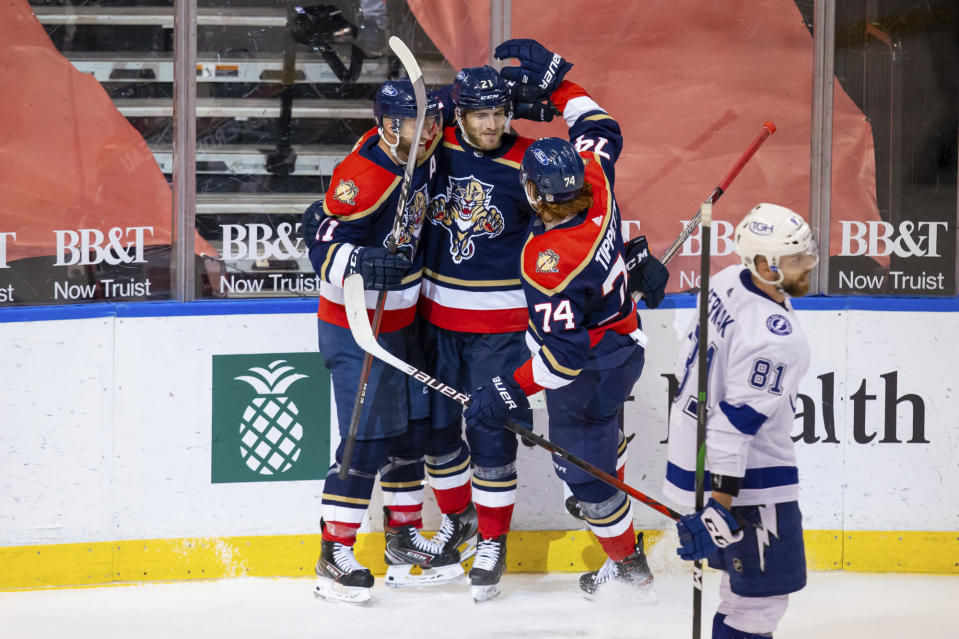 Florida Panthers center Alex Wennberg (21) celebrates a hat trick with left wing Jonathan Huberdeau (11) and right wing Owen Tippett (74) during the third period of an NHL hockey game against the Tampa Bay Lightning, Saturday, May 8, 2021, in Sunrise, Fla. (AP Photo/Mary Holt)