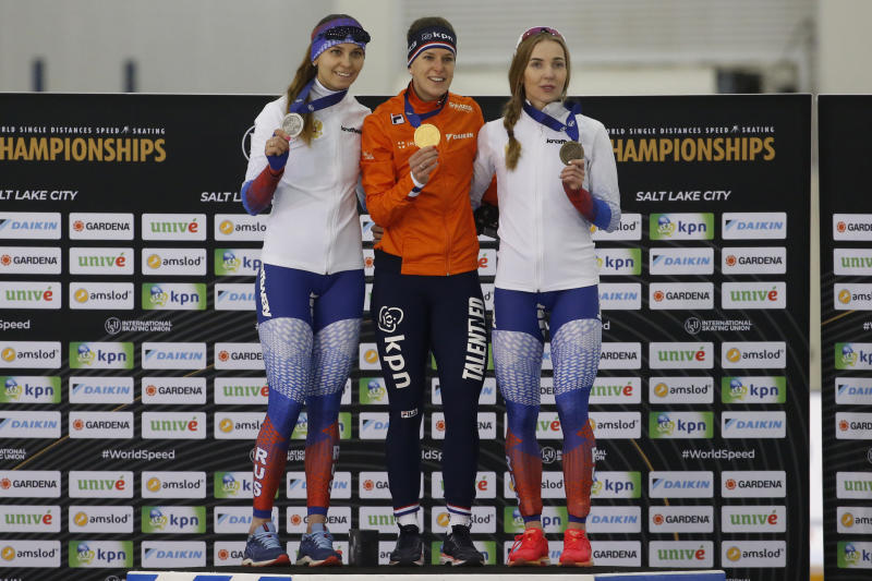First-place finisher Netherlands' Ireen Wust, center, shares the podium with second-place finisher Evgeniia Lalenkova, left, and third-place finisher Elizaveta Kazelina following the women's 1,500 meters during the world single distances speedskating championships Sunday, Feb. 16, 2020, in Kearns, Utah. (AP Photo/Rick Bowmer)