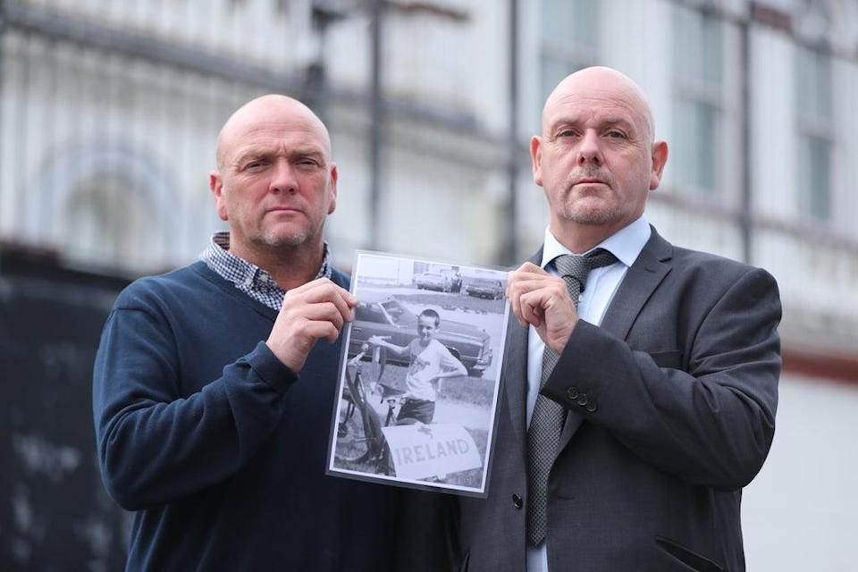 Joe (left) and Kieran Geddis hold a picture of their brother Stephen outside Banbridge Court, where a fresh inquest into his death is being held (Niall Carson/PA) (PA Wire)