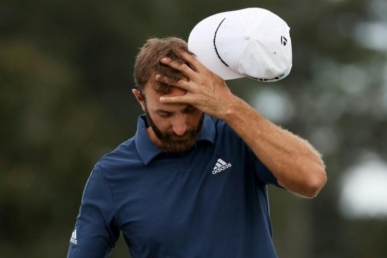 Top-ranked defending champion Dustin Johnson reacts after his third bogey in four holes at the par-4 18th Friday to miss the cut at the 85th Masters