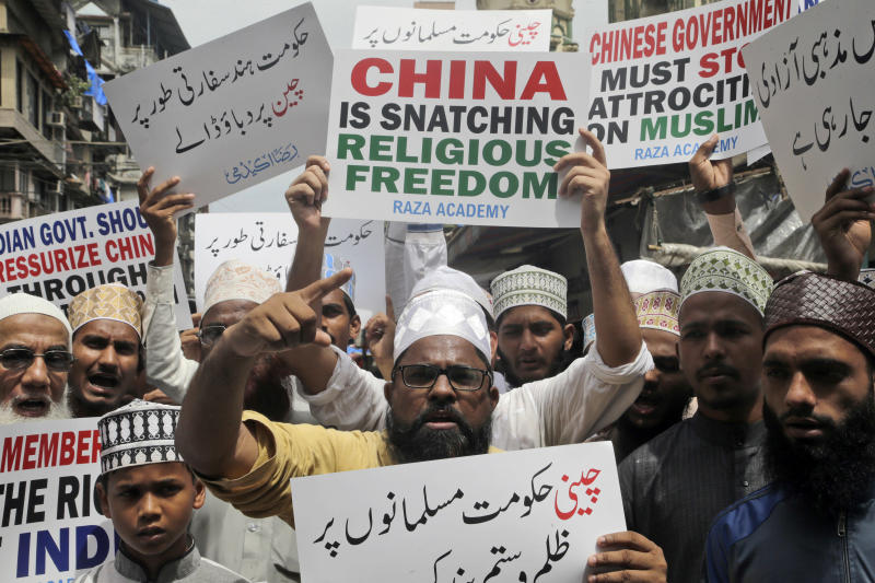 FILE - In this Sept. 14, 2018, file photo, Indian Muslims shout slogans in support of minority Uighur Muslim ethnic groups in detention and political indoctrination centers in China. Members of the Uighur Muslim ethnic group are calling on China to post videos of their relatives who have disappeared into a vast system of internment camps. The campaign follows the release of a state media video showing famed Uighur musician Abdurehim Heyit, who many believed had died in custody. (AP Photo/Rajanish Kakade, File)
