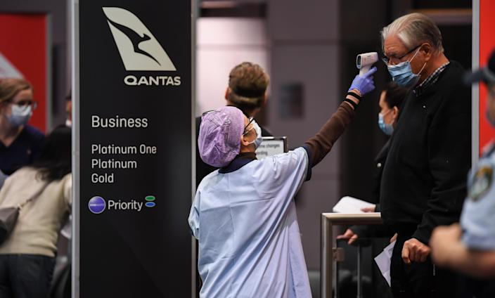 Passengers have their temperature checked by health officials as they arrive from a Qantas flight at Sydney Airport on one of the last flights out of Melbourne to Sydney. (Getty)