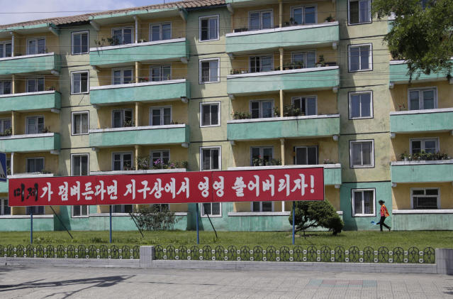 "In this June 21, 2018 photo, a woman walks outside an apartment building where an anti-U.S. propaganda banner is put up in Pyongyang, North Korea. In another sign of detente following the summit between leader Kim Jong Un and U.S. President Donald Trump, North Korea has cancelled one of the most symbolic and politically charged events of its propaganda calendar: the annual ""anti-U.S. imperialism"" rally marking the start of the Korean War. Writings on the banner read: ""If the U.S. imperialists try to invade our country, let's sweep them off the face of the Earth."" (AP Photo/Dita Alangkara)"