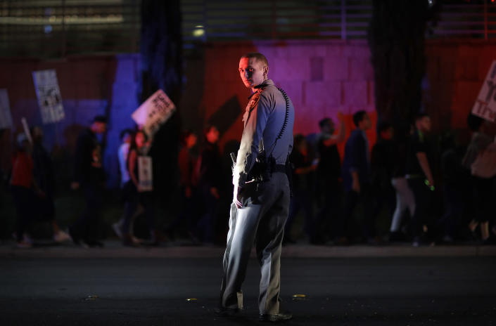 <p>A Las Vegas police officer stands on duty as protesters against President-elect Donald Trump march near the Las Vegas Strip, Saturday, Nov. 12, 2016, in Las Vegas. Tens of thousands of people marched in streets across the United States on Saturday, staging the fourth day of protests of Trump's surprise victory as president. (AP Photo/John Locher) </p>