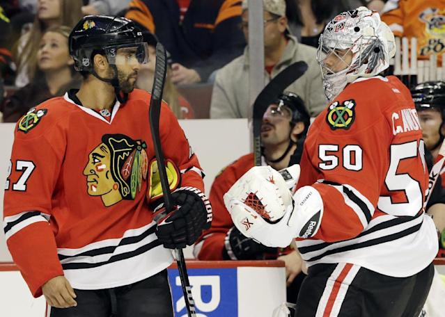 Chicago Blackhawks goalie Corey Crawford, right, talks with Johnny Oduya during the first period of an NHL hockey game against the Phoenix Coyotes in Chicago, Thursday, Nov. 14, 2013. (AP Photo/Nam Y. Huh)