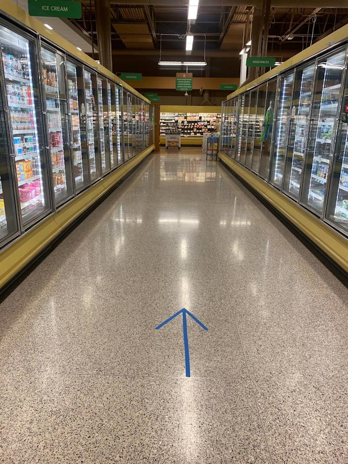 Because of the chance to spread the coronavirus, warning signs addressing social distancing hang in the aisles and directional signs on the floors ask customers to all go the same direction in Publix grocery stores around Charlotte on Wednesday, April 8, 2020.