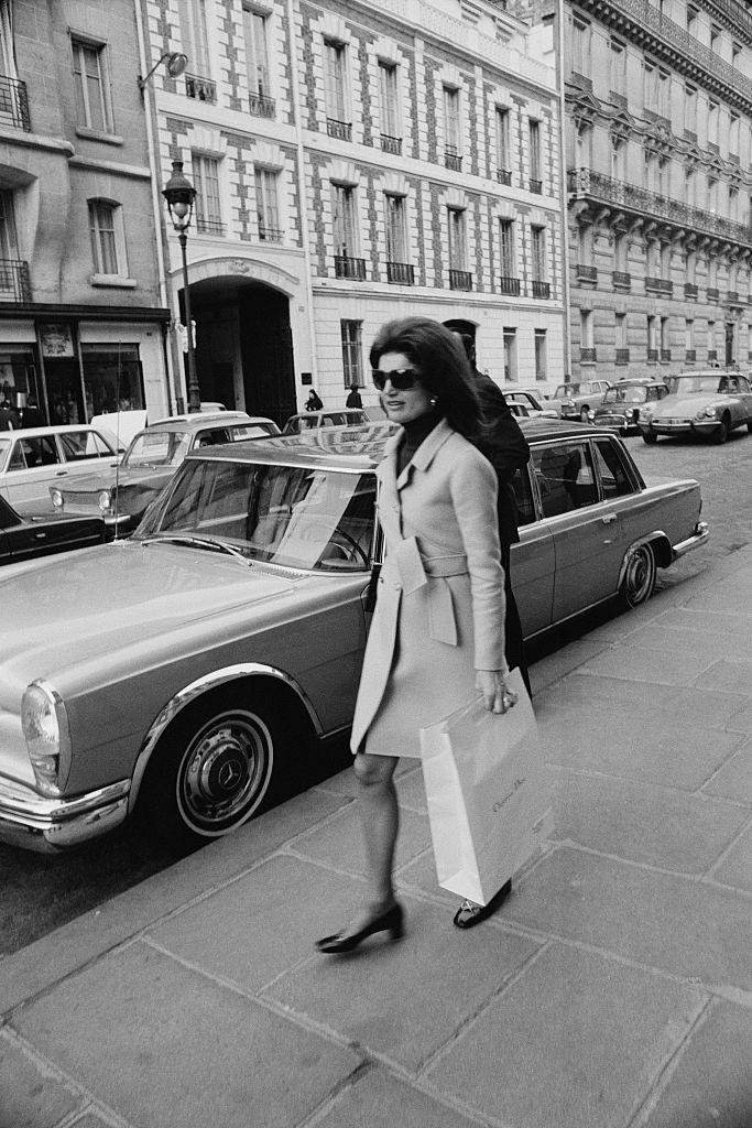<p>American royalty, Jackie Kennedy, sports a chic trench coat and her signature sunglasses as she steps out for a day of shopping in Paris. </p>