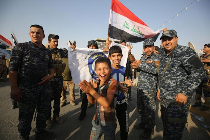 """Iraqi federal police members and civilians celebrate in the Old City of Mosul on 9 July 2017 after the government's announcement of the """"liberation"""" of the embattled city. Iraqi Prime Minister Haider al-Abadi's office said he was in """"liberated"""" Mosul to congratulate """"the heroic fighters and the Iraqi people on the achievement of the major victory"""": AFP/Getty Images"""