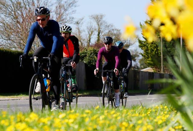 Cyclists pass a bank of daffodils in Paley Street, Berkshire