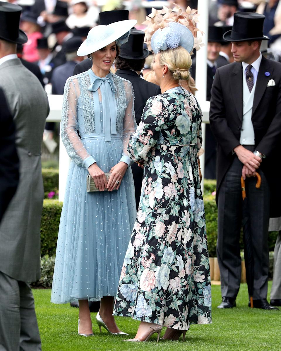 The Duchess of Cambridge (left) speaks to Zara Tindall whilst attending day one of Royal Ascot at Ascot Racecourse.
