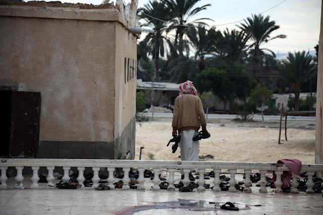 <p>A man collects the remains of belongings of victims from Al-Rawda mosque a day after the mosque was attacked in the northern city of Arish, Sinai Peninsula, Egypt, Nov. 25, 2017. (Photo: Ahmed Hassan/EPA-EFE/REX/Shutterstock) </p>