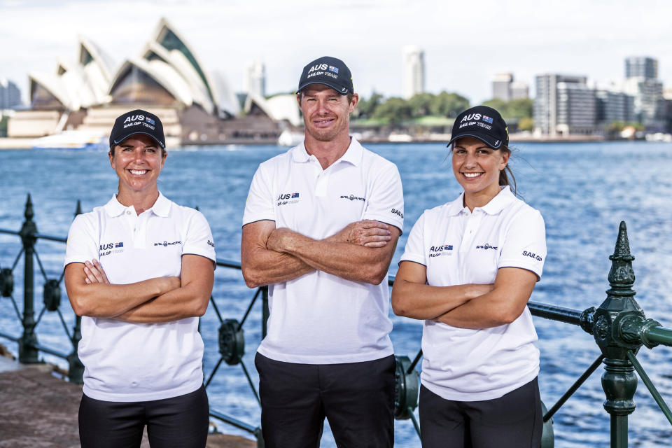 In this photo provided by Sail GP are Nina Curtis, left, and Lisa Darmanin, right, posing with helmsman and CEO Tom Slingsby at Sydney Harbour Wednesday, April 7, 2021, in Australia. Four years ago, the closest Australian Olympic sailing medalists Darmanin and Curtis could get to the America's Cup was by taking jobs in a hospitality lounge on site in Bermuda. They'll be back in Bermuda in just a few days, this time with the defending champion Australian team in SailGP as part of a developmental program designed to fast-track the inclusion of women into the global league. (SailGP via AP)