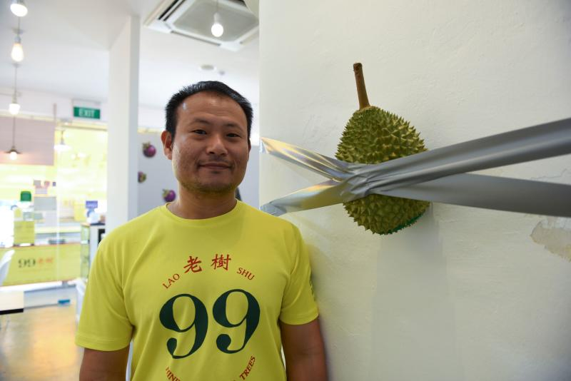 "This photo taken on December 12, 2019 shows Singaporean Kelvin Tan, the co-owner of 99 Old Trees, a durian shop in Singapore, posing with his parody of the 120,000 USD artwork Comedian by Maurizio Cattelan. - Inspired by a 120,000 USD artwork, a banana taped to a wall, Tan put his own spin on the piece, captioning it ""looks like art, smells like fart"" in a widely-shared post. (Photo by CATHERINE LAI/AFP via Getty Images)"