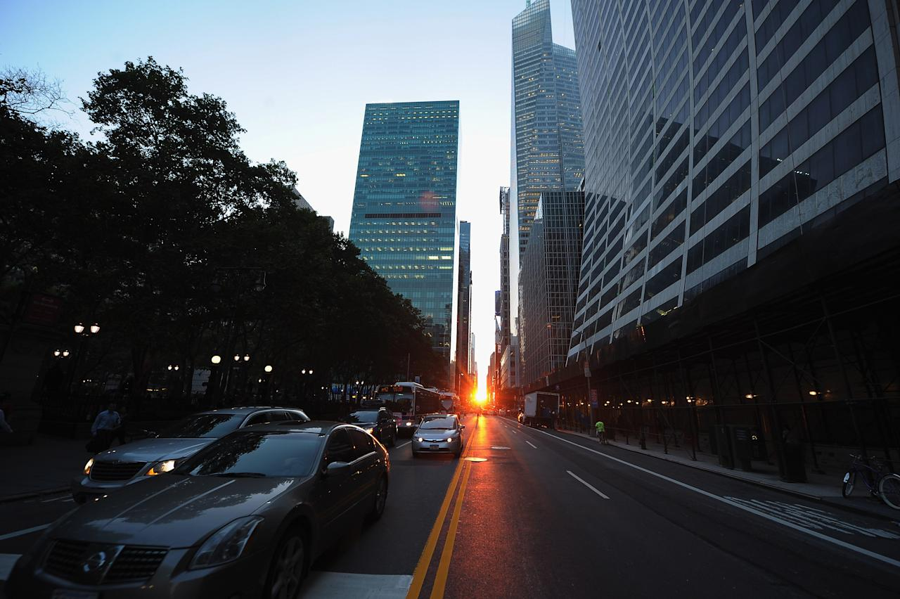 "The sun sets during ""Manhattanhenge"" on July 12, 2011 in New York City. The Manhattan Solstice is a semiannual occurrence in which the setting sun aligns west-east with the street grid of the city.  (Photo by Michael Loccisano/Getty Images)"