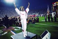 Whitney Houston sings the National Anthem during the pregame show at Super Bowl XXV while tens of thousands of football fans wave tiny American flags in an incredible outburst of patriotism during the Persian Gulf War on 01/27/1991. (Photo by Michael Zagaris/Getty Images)
