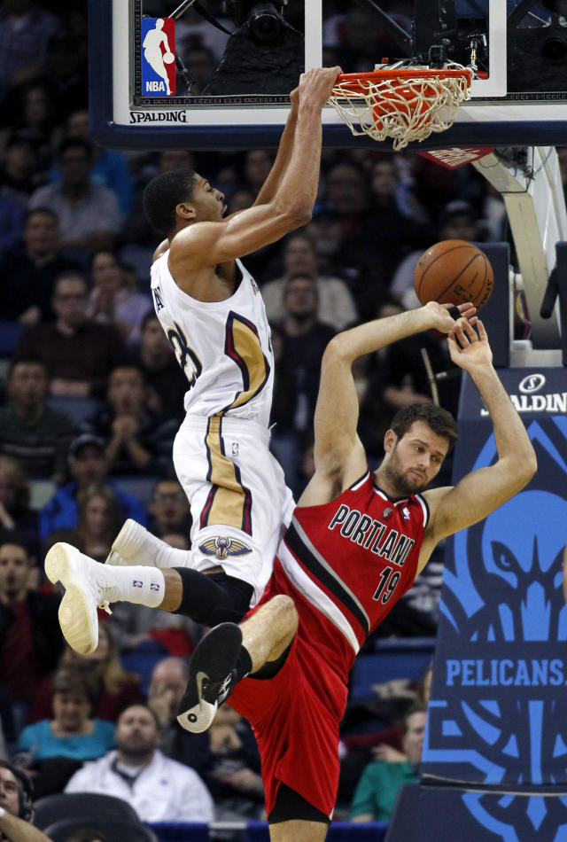 New Orleans Pelicans forward Anthony Davis (23) slam dunks over Portland Trail Blazers center Joel Freeland (19) in the first half of an NBA basketball game in New Orleans, Monday, Dec. 30, 2013. (AP Photo/Gerald Herbert)
