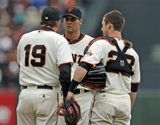 San Francisco Giants starting pitcher Ryan Vogelsong, center, talks to pitching coach Dave Righetti, left, and catcher Buster Posey after giving up two runs to the Chicago Cubs during the second inning of a baseball game in San Francisco, Monday, June 4, 2012. (AP Photo/Marcio Jose Sanchez)