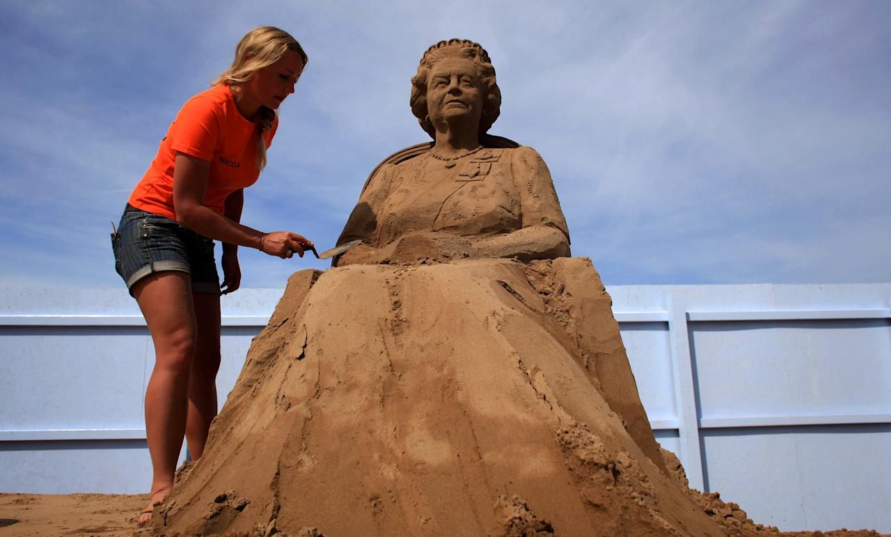 WESTON-SUPER-MARE, ENGLAND - MAY 28:  Sand sculpture artist Nicola Wood completes a sand sculpture she has created of Queen Elizabeth II at the annual Weston-super-Mare Sand Sculpture festival on May 28, 2012 in Weston-Super-Mare, England. Now in its seventh year, the festival, which opens to the public on Friday, features sand sculptures from award-winning artists from across the globe. Using 4000 tonnes of Weston beach sand this year's giant sand art display, created by 15 international artists on the theme Fun and Games, runs throughout the summer until September 9.  (Photo by Matt Cardy/Getty Images)