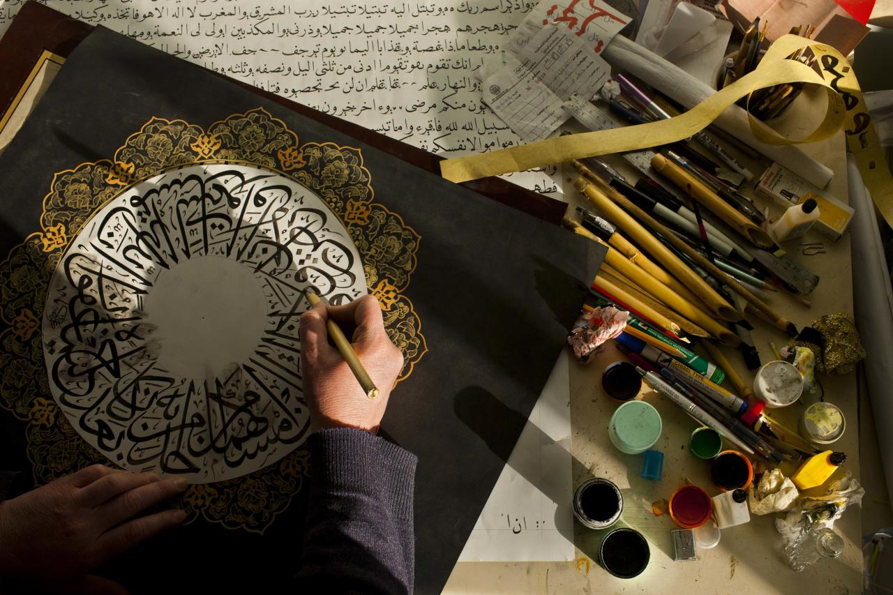 """In this Thursday, Jan. 26 2012 photo, Palestinian calligraphy expert Adel Fauzy practices at his studio in the West Bank town of Hawara, near Nablus. Parchment, feathers and """"qalams,"""" a pen made of dried bamboo, are still used by sophers Jewish scribes and khattats Muslim calligraphers. AP Photo/Bernat Armangue)"""