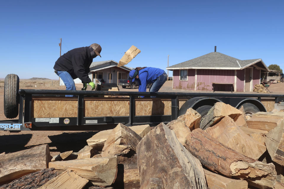 Allen Benally, left, and Clara Tsosie unload wood from a flatbed trailer in Teesto, Ariz., on the Navajo Nation, on Thursday, Feb. 11, 2021. Teesto workers, health representatives, volunteers and neighbors keep close tabs on another to ensure the most vulnerable citizens get the help they need. (AP Photo/Felicia Fonseca)