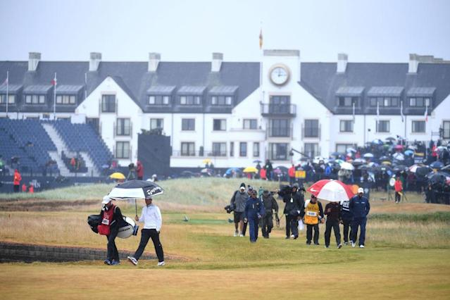 Rory McIlroy walks on a soggy Carnoustie. (Getty)