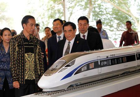 FILE PHOTO: Indonesian President Joko Widodo and the general manager of China Railway Corp. Sheng Guangzu stand next to a train model as they attend a groundbreaking ceremony for the Jakarta-Bandung fast-train railway line in Walini, West Java province