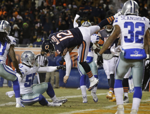 Chicago Bears quarterback Josh McCown (12) gets hit by Dallas Cowboys linebacker Sean Lee (50) in the air as McCown makes a touchdown run during the first half of an NFL football game, Monday, Dec. 9, 2013, in Chicago. (AP Photo/Nam Y. Huh)