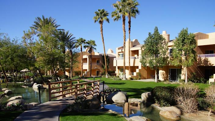 RANCHO MIRAGE, CALIFORNIA - DEC 16, 2015 - Southwestern style hotel buildings with ponds in green oasis with Palm trees, Rancho Mirage, California - Image.