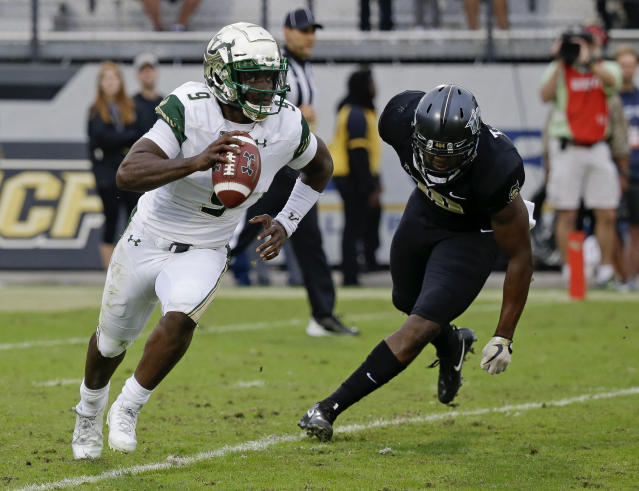 """South Florida quarterback <a class=""""link rapid-noclick-resp"""" href=""""/ncaaf/players/245945/"""" data-ylk=""""slk:Quinton Flowers"""">Quinton Flowers</a> (9) scrambles looking for a receiver as he is pressured by Central Florida linebacker <a class=""""link rapid-noclick-resp"""" href=""""/nfl/players/28678/"""" data-ylk=""""slk:Titus Davis"""">Titus Davis</a>, right, during the first half of an NCAA college football game, Friday, Nov. 24, 2017, in Orlando, Fla. (AP Photo/John Raoux)"""
