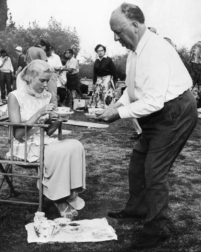 <p>Legendary director Alfred Hitchcock joins his leading lady, Grace Kelly, for tea on the set of <em>To Catch a Thief</em>.  </p>