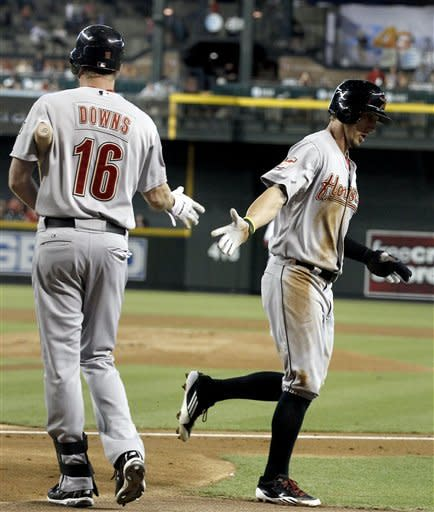 Houston Astros' Jordan Schafer, right, shakes hands with teammate Matt Downs (16) after scoring a run against the Arizona Diamondbacks during the first inning in a baseball game on Friday, July 20, 2012, in Phoenix. (AP Photo/Ross D. Franklin)